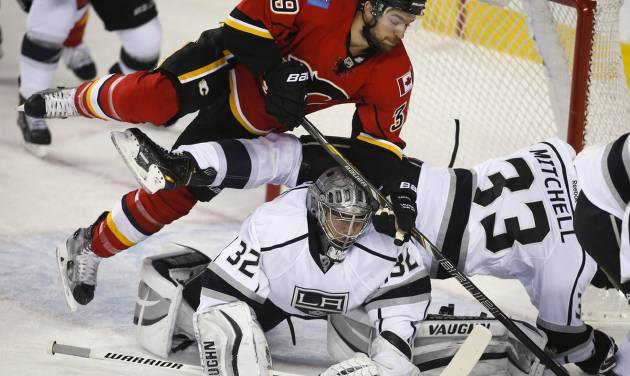 Los Angeles Kings goalie Jonathan Quick, center, ducks as teammate Willie Mitchell, right, and Calgary Flames' TJ Galiardi crash over him during the first period of an NHL hockey game Thursday, Feb. 27, 2014, in Calgary, Alberta. (AP Photo/The Canadian Press, Jeff McIntosh)