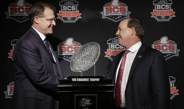 Auburn head coach Gus Malzahn, left, and Florida State head coach Jimbo Fisher shake hands in front of The Coaches' Trophy during a news conference for the NCAA BCS National Championship college football game Sunday, Jan. 5, 2014, in Newport Beach, Calif. Florida State plays Auburn on Monday, Jan. 6, 2014. (AP Photo/David J. Phillip)