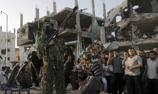 A Palestinian militant of Izzedine al-Qassam Brigades, military wing of Hamas, holds his rifle during a celebration of the victory rally at the debris of destroyed houses in Shijaiyah, neighborhood of Gaza City, in the northern Gaza Strip, Wednesday, Aug. 27, 2014. An open-ended cease-fire between Israel and Palestinian militants in the Gaza Strip was holding Wednesday. (AP Photo/Adel Hana)
