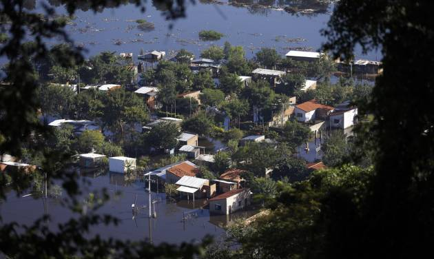CORRECTS SPELLING OF LAMBARE -  Homes are surrounded by floodwater in the Cateura neighborhood, seen from Lambare Hill in Asuncion, Paraguay, Tuesday, June 10, 2014. Thousands of people living along the Paraguay River have been affected by flooding after the river overflowed its banks. (AP Photo/Jorge Saenz)