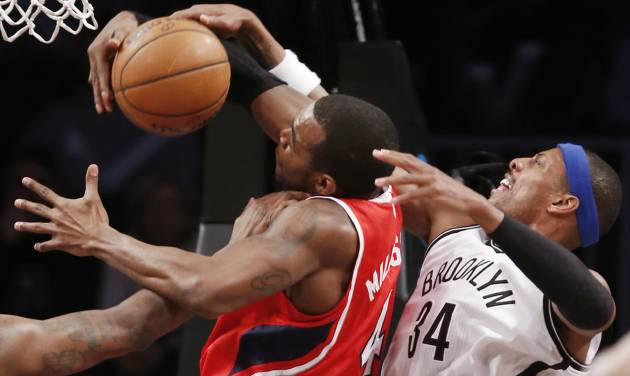 Brooklyn Nets forward Paul Pierce (34) defends Atlanta Hawks forward Paul Millsap (4) in the first half of their NBA basketball game at the Barclays Center, Monday, Jan. 6, 2014, in New York. (AP Photo/Kathy Willens)