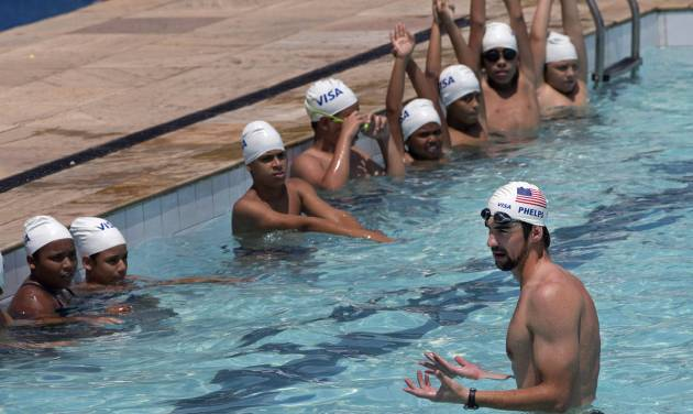 U.S. Olympic swimming champion Michael Phelps speaks to young swimmers in the pool at the Olympic Village Carlos Castilho where they regularly train in the Complexo de Alemao slum as he leads a workshop sponsored by Visa in Rio de Janeiro, Brazil, Tuesday, Oct. 30, 2012. (AP Photo/Silvia Izquierdo)