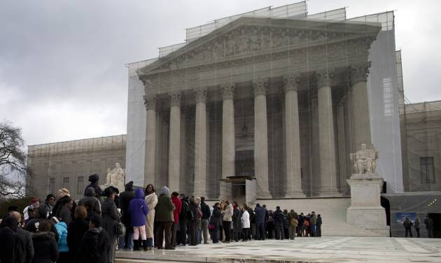 FILE – In this Feb. 27, 2013, file photo people wait in line outside the Supreme Court in Washington. Half a century ago in a landmark decision, Gideon v. Wainwright on March 18, 1963, the Supreme Court guaranteed a lawyer for criminal defendants who are too poor to afford one. But in many states today, taxpayer-funded public defenders face crushing caseloads, the quality of legal representation varies from county to county and people stand before judges having seen a lawyer only briefly, if at all. (AP Photo/Evan Vucci, File)
