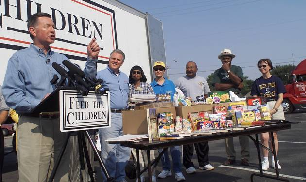 Feed the Children founder Larry Jones speaks to volunteers before giving out boxes of food & school supplies. By Steve Gooch