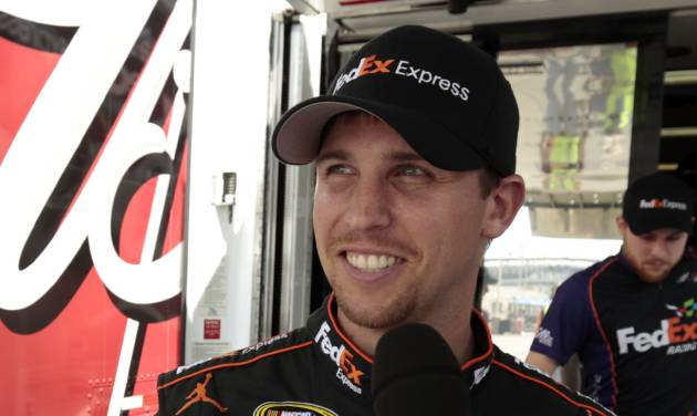 Denny Hamlin smiles while being interviewed after winning the pole for Sunday's NASCAR Sprint Cup Series auto race at Indianapolis Motor Speedway in Indianapolis, Saturday, July 28, 2012. (AP Photo/AJ Mast)
