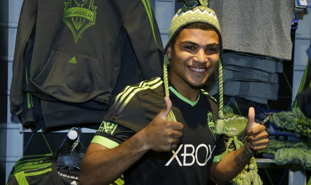 "FILE - In this March 3, 2014 file photo, Seattle Sounders' DeAndre Yedlin adds a hat to his modeling of the MLS soccer team's new ""third kit"" uniform at the CenturyLink Field Pro Shop in Seattle. Yedlin is back with the  Sounders but far more known than when he left for U.S. national team camp nearly two months ago. After an impressive performance in the World Cup, the question now is how long can Seattle hold on to its budding homegrown star?  (AP Photo/Ted S. Warren, File)"