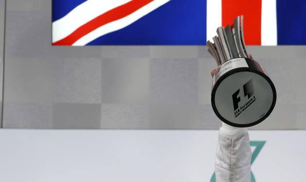 Mercedes driver Lewis Hamilton of Britain gestures as he holds his trophy aloft after winning the Malaysian Formula One Grand Prix at Sepang International Circuit in Sepang, Malaysia, Sunday, March 30, 2014. (AP Photo/Vincent Thian)