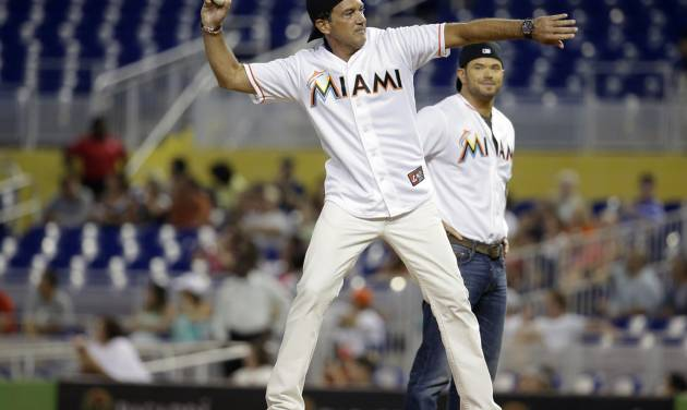 Actor Antonio Banderas, left, throws out a ceremonial pitch before a baseball game between the Miami Marlins and St. Louis Cardinals, Wednesday, Aug. 13, 2014, in Miami. At right is actor Kellan Lutz. (AP Photo/Lynne Sladky)