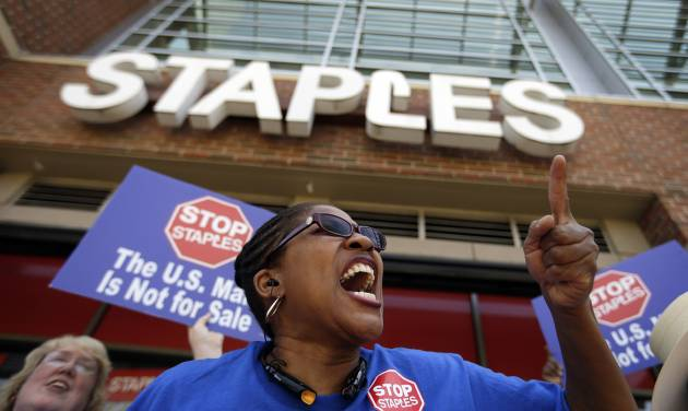 "U.S. Post Office employee Detra Parker chants during a protest outside a Staples store, Thursday, April 24, 2014, in Atlanta. Thousands of postal workers picketed outside Staples stores nationwide Thursday to protest a pilot program that allows the office supply chain to handle U.S. mail. The American Postal Workers Union fears layoffs and post office closings and says that unlike retail workers, postal workers ""have taken an oath to protect the sanctity of the mail."" (AP Photo/David Goldman)"