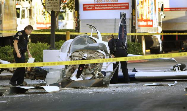 San Diego police examine the wreckage of a small plane in the parking lot of shopping center Wednesday, July 30, 2014, in San Diego. Police said that one woman was killed and one hurt in the crash. (AP Photo/U-T San Diego, David Brooks) NO SALES; MANDATORY CREDIT; TV OUT; MAGAZINES OUT; COMMERCIAL INTERNET OUT
