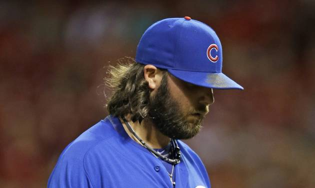 Chicago Cubs relief pitcher James Russell walks to the dugout at the end of the seventh inning of a baseball game against the Cincinnati Reds, Monday, July 7, 2014, in Cincinnati. Russell gave up a two-run home run to Jay Bruce in the inning. Cincinnati won 9-3. (AP Photo/Al Behrman)