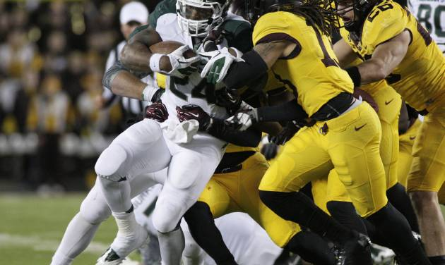 Michigan State running back Le'Veon Bell (24) is gang-tackled during the second half of an NCAA college football game against Minnesota, Saturday, Nov. 24, 2012, in Minneapolis. Michigan State won 26-10. (AP Photo/Paul Battaglia)