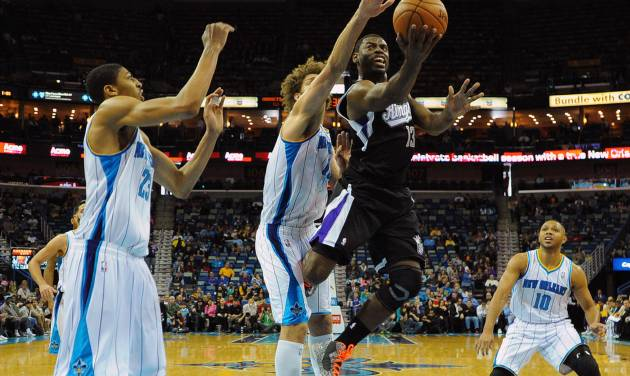 Sacramento Kings guard Tyreke Evans (23) shoots as New Orleans Hornets center Robin Lopez, center left, defends  as Hornets Anthony Davis, left, looks on in the first half of an NBA basketball game in New Orleans, Monday Jan. 21, 2013.  (AP Photo / Stacy Revere)