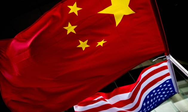 In this Nov. 7, 2012 photo, U.S. and Chinese national flags are hung outside a hotel during the U.S. Presidential election event, organized by the U.S. embassy in Beijing. As public evidence mounts that the Chinese military is responsible for stealing massive amounts of U.S. government data and corporate trade secrets, the Obama administration is eyeing fines and other trade actions it may take against Beijing or any other country guilty of cyberespionage. The Chinese government, meanwhile, has denied involvement in the cyber-attacks tracked by Mandiant. Instead, the Foreign Ministry said that China, too, is a victim of hacking, some of it traced to the U.S. Foreign Ministry spokesman Hong Lei cited a report by an agency under the Ministry of Information Technology and Industry that said in 2012 alone that foreign hackers used viruses and other malicious software to seize control of 1,400 computers in China and 38,000 websites. (AP Photo/Andy Wong)