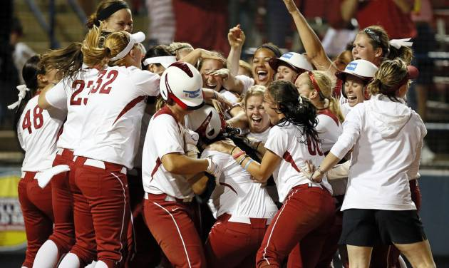 The OU Sooners surround Lauren Chamberlain (44), middle, after Chamberlain hit the game-winning home run in the twelfth inning during Game 1 of the Women's College World Series NCAA softball championship series between Oklahoma and Tennessee at ASA Hall of Fame Stadium in Oklahoma City, Monday, June 3, 2013. OU won 5-3 in 12 innings. Photo by Nate Billings, The Oklahoman