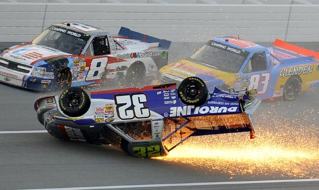 Max Gresham (8) and Chris Fontaine (83) get past a tumbling Miguel Paludo (32) on the final lap of the NASCAR Trucks auto race at Talladega Superspeedway in Talladega, Ala., Saturday, Oct. 19, 2013. (AP Photo/Dan Lighton)