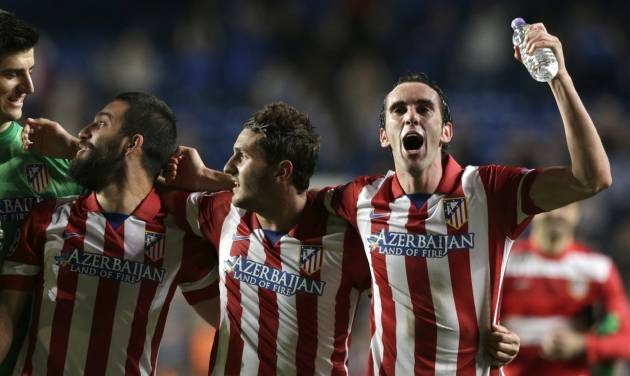 Atletico goalkeeper Thibaut Courtois, left looks at Atletico's Arda Turan, second left as they celebrate after they defeated Chelsea in the Champions League semifinal second leg soccer match between Chelsea and Atletico Madrid at Stamford Bridge stadium in London, Wednesday, April 30, 2014. (AP Photo/Matt Dunham)