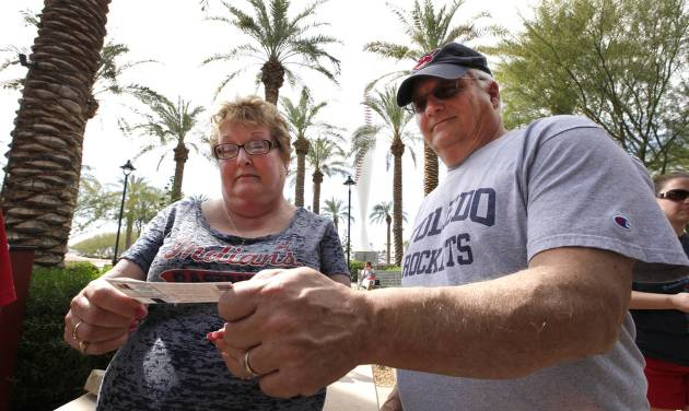 In this photo taken Wednesday, Feb. 26, 2014, Sue Knieriemen, of Fremont, Ohio, and her brother Charles Bork, of Sylvania, Ohio, check their tickets outside Goodyear Ballpark before an exhibition baseball game between the Cincinnati Reds and the Cleveland Indians in Goodyear, Ariz. After such a long, cold season, Americans across the winter-weary Midwest and the East Coast are desperate to escape to warm-weather destinations in California, Arizona and Florida. (AP Photo/Paul Sancya)
