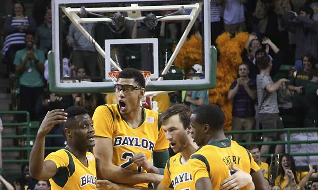 Baylor guard Brady Heslip (5) huddles with teammatesIsaiah Austin (21), Gary Franklin, left, and Kenny Chery, right, after scoring on a 3-point play in the second half of an NCAA college basketball game, Saturday, Feb. 15, 2014, in Waco, Texas. (AP Photo/Waco Tribune Herald, Rod Aydelotte)