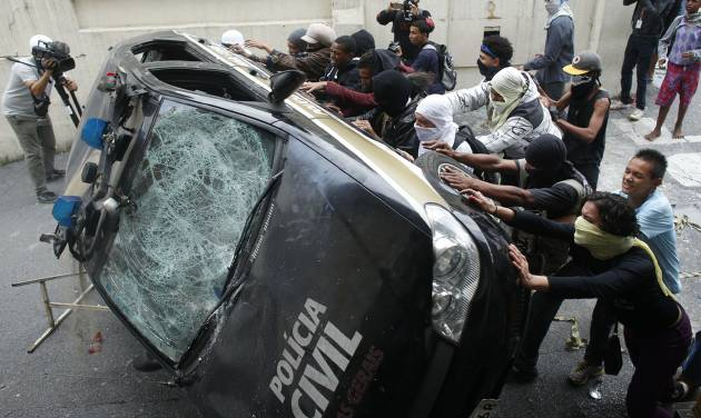 Demonstrators push over a police car during a protest demanding better public services and against the money spent on the World Cup soccer tournament in Belo Horizonte, Brazil, Thursday, June, 12, 2014. (AP Photo/Victor R. Caivano)