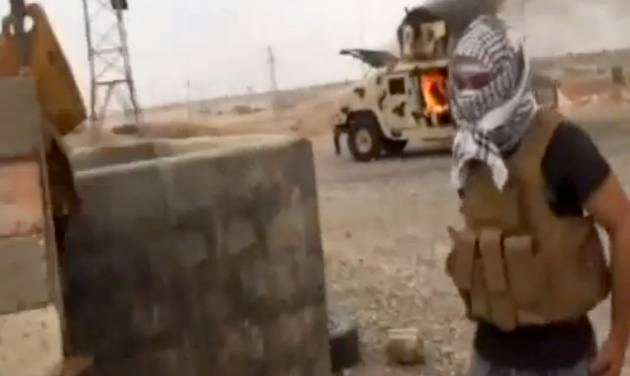 This image made from video posted by Iraqi0Revolution, a group supporting the al-Qaida breakaway Islamic State of Iraq and the Levant (ISIL) on Wednesday, June 11, 2014, which has been verified and is consistent with other AP reporting, shows a militant standing in front of a burning Iraqi Army Humvee in Tikrit, Iraq. The al-Qaida-inspired group that led the charge in capturing two key Sunni-dominated cities in Iraq this week has vowed to march on to Baghdad, raising fears about the Shiite-led government's ability to slow the assault following lightening gains. Fighters from ISIL on Wednesday took Saddam Hussein's hometown of Tikrit, as soldiers and security forces abandoned their posts and yielded ground once controlled by U.S. forces. (AP Photo/Iraqi0Revolution via AP video)