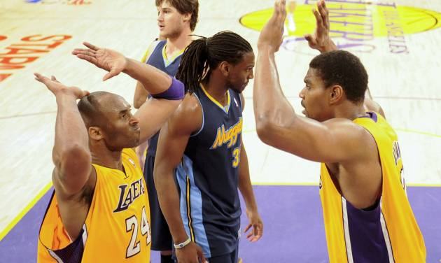 Los Angeles Lakers' Kobe Bryant, left, celebrates with Andrew Bynum, as Denver Nuggets' Kenneth Faried, middle, looks away during the second half of a NBA first-round playoff basketball game in Los Angeles, Tuesday, May 1, 2012. The Lakers won 104-100. (AP Photo/Chris Carlson)