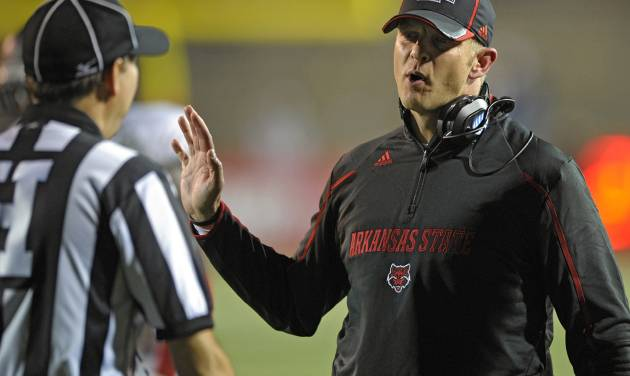 FILE - In this Nov. 2, 2013 file photo, Arkansas State head coach Bryan Harsin talks with linesman Scott Peterson during a timeout with South Alabama in the second quarter of an NCAA college football game in Mobile, Ala. A person familiar with the decision tells The Associated Press that Boise State has hired  Harsin as its next coach. The person spoke on condition of anonymity because the move had not become official. (AP Photo/G.M. Andrews, File)
