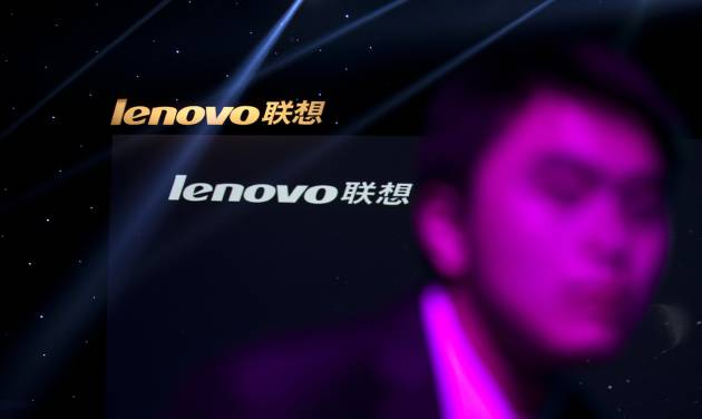 FILE - In this Aug. 6, 2012 file photo, a Lenovo employee, front, walks near the company logos during a Lenovo promotional event in Beijing, China. Lenovo said Thursday Jan. 23, 2014  it is acquiring IBM's x86 server business and expects to offer jobs to 7,500 IBM employees in locations around the world. (AP Photo/Alexander F. Yuan, File)