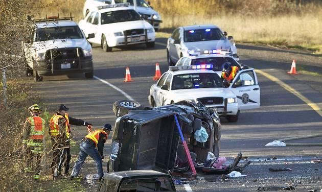 In this Dec. 4, 2013 photo, crews respond to an accident in Vancouver, Wash. Caran Johnson who regularly monitors police scanner traffic unknowingly live-tweeted about her husband's death in the freeway crash. (AP Photo/The Columbian, Zachary Kaufman)