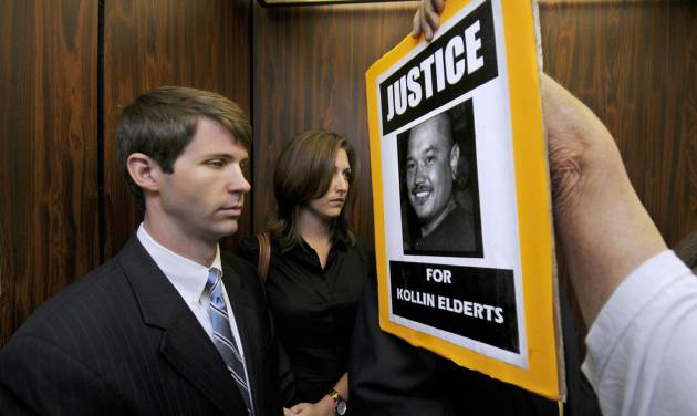 FILE- In this Nov. 17, 2011 file photo, an unidentified protester shoves a sign in the face of State Department Special Agent Christopher Deedy, left, and his wife on an elevator in Honolulu. Deedy, of Arlington, Va., is back in Honolulu to stand trial a second time for killing Kollin Elderts during an altercation in a McDonald's restaurant. He contends the shooting was self-defense. Free on $250,000, bail, he returned home after the first trial. (AP Photo/Honolulu Star Advertiser, Dennis Oda, File)