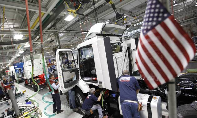 In a Jan. 6, 2011 photo workers install parts on a truck on the Volvo truck assembly line at the Volvo plant in Dublin, Va. The government on Friday will make its first estimate of growth for the January-March quarter. (AP Photo/Steve Helber)