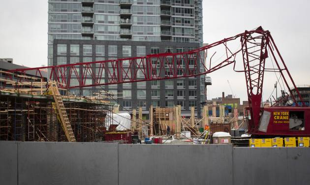 A mangled crane lies at the construction site in the Queens borough of New York where it collapsed, Wednesday, Jan. 9, 2013. The Fire Department of New York says the 200-foot crane collapsed onto a building under construction, injuring seven people, three of them seriously. (AP Photo/John Minchillo)