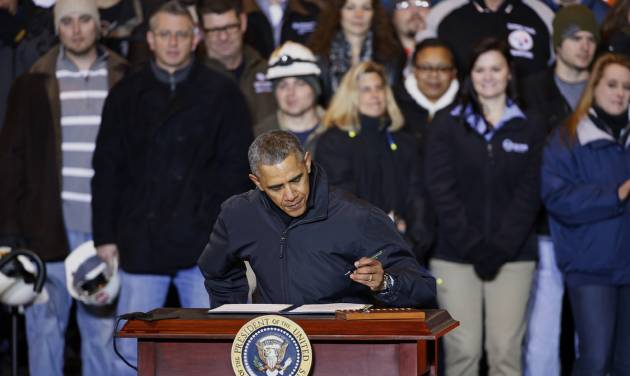 President Barack Obama prepares to sign an executive order mandating that federal contractors be required to raise the minimum wage they pay their workers to $10.10, Wednesday, Jan. 29, 2014, at the end of an appearance at the US Steel's Mon Valley Works in West Mifflin, Pa. (AP Photo/Gene J. Puskar)