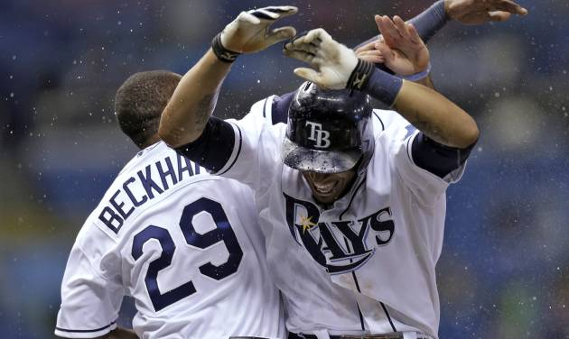 Tampa Bay Rays' Desmond Jennings, right, celebrates with Tim Beckham after singling in the game-winning run off Texas Rangers relief pitcher Joe Ortiz during a baseball game Wednesday, Sept. 18, 2013, in St. Petersburg, Fla. Rays' Sam Fuld scored. The Rays won 4-3 in 12 innings. (AP Photo/Chris O'Meara)