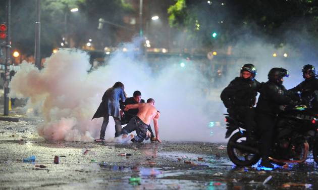 Soccer fans try to escape from a tear gas cloud and a police water cannon, used to restrain a group of youths who hurled rocks and vandalized stores, at a rally after Argentina's performance in a 1-0 loss to Germany in the World Cup finals, Sunday, July 13, 2014, in Buenos Aires, Argentina. Police said more than a dozen officers were injured and many more were arrested. (AP Photo/Victor Carreira)