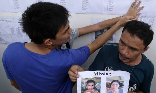 Roderick Mama holds print out of his missing wife and sons as a couple checks the list of survivors posted on the wall of the 2GO shipping company Sunday Aug. 18, 2013 in Cebu city, central Philippines. Roderick's 8-month old son Dincell survived Friday night's collision between the passenger ferry MV Thomas Aquinas and the cargo ship Sulpicio Express Siete in central Philippines.  Divers plucked two more bodies from a sunken passenger ferry on Sunday and scrambled to plug an oil leak in the wreckage after a collision with a cargo ship. The accident near the central Philippine port of Cebu that has left 34 dead and more than 80 others missing. (AP Photo/Bullit Marquez)