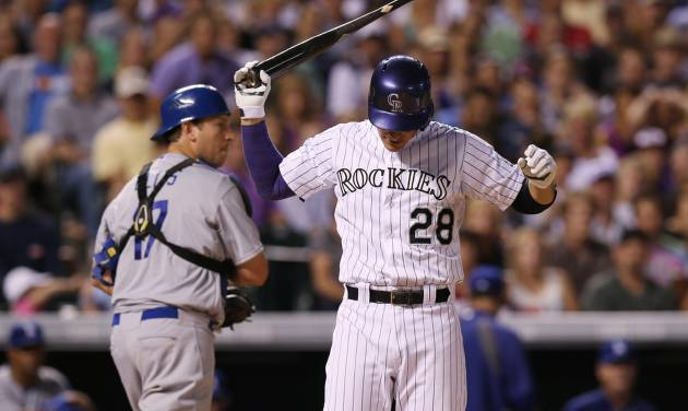 Colorado Rockies' Nolan Arenado, front, reacts after striking out with two runners on base as Los Angeles Dodgers catcher A.J. Ellis heads to the dugout at the end of the eighth inning of the Dodgers' 3-2 victory in a baseball game in Denver on Thursday, July 3, 2014. (AP Photo/David Zalubowski)