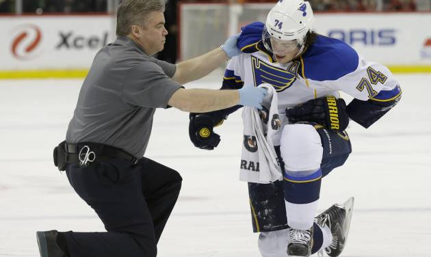 St. Louis Blues right wing T.J. Oshie (74) tries to get up with help from a trainer but can't after being injured during the second period of an NHL hockey game against the Minnesota Wild in St. Paul, Minn., Thursday, April 10, 2014. (AP Photo/Ann Heisenfelt)