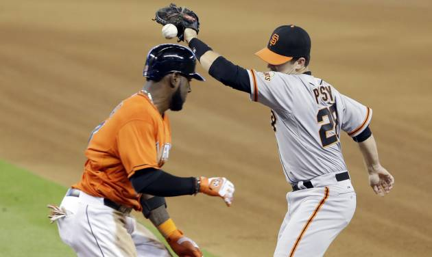 Miami Marlins' Marcell Ozuna, left, reaches first base on an error by San Francisco Giants first baseman Buster Posey, right, during the fourth inning of a baseball game, Sunday, July 20, 2014 in Miami. (AP Photo/Wilfredo Lee)