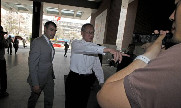 """Robert S. Wang, center, deputy chief of mission at the U.S. embassy in Beijing, gestures as he walks with an unidentified U.S. embassy staff, left, outside the hospital where blind activist lawyer Chen Guangcheng is recuperating in Beijing Friday, May 4, 2012. The Chinese activist at the center of a diplomatic standoff between the United States and China said Friday his situation is """"dangerous,"""" and that American officials have been blocked from seeing him for two days and friends who have tried to visit have been beaten up. (AP Photo/Ng Han Guan)"""