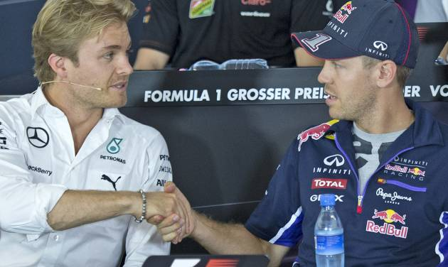 World Championship leader and Mercedes Formula One driver Nico Rosberg of Germany, left, shakes hands with Red Bull Formula One driver Sebastian Vettel of Germany, right, during a press conference in Hockenheim, Germany, Thursday, July 17, 2014. The German Grand Prix will be held on Sunday, July 20, 2014. (AP Photo/Jens Meyer)