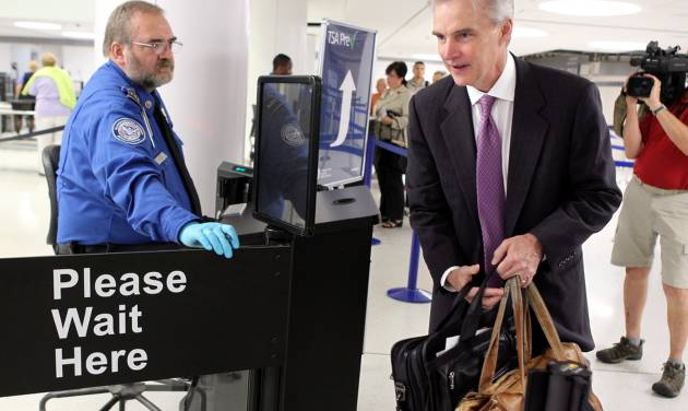 FILE - In this July 31, 2012 file photo, Transportation Security Administration agent Kevin Effan, left, allows a screened passenger to board his American Airlines flight via the new TSA PreCheck lane at Concourse C security checkpoint at Lambert-St. Louis International Airport on its first day of operation.  The TSA is expanding its PreCheck expedited screening program to passengers on international airlines. Air Canada on Tuesday, April 29, 2014 became the first international carrier to participate, with TSA officials saying other international airlines would soon sign on.  (AP Photo/St. Louis Post-Dispatch, Christian Gooden, File) EDWARDSVILLE INTELLIGENCER OUT; THE ALTON TELEGRAPH OUT