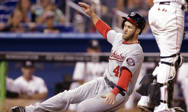 Washington Nationals' Bryce Harper scores on a throwing error by  Miami Marlins' center fielder Marcell Ozuna in the eighth inning during the of the MLB National League baseball game, Tuesday, April 15, 2014, in Miami. The Marlins defeated the Nationals 11-2. (AP Photo/Lynne Sladky)