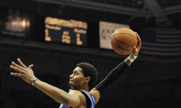 Oklahoma City Thunder's Jeremy Lamb dunks the ball over in front of Milwaukee Bucks' Gary Neal (12) during the first half of an NBA basketball game Saturday, Nov. 16, 2013, in Milwaukee. (AP Photo/Jim Prisching)