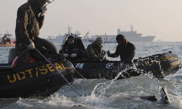 Divers look for people believed to have been trapped in the sunken ferry Sewol in the water off the southern coast near Jindo, south of Seoul, South Korea, Wednesday, April 23, 2014. The grim work of recovering bodies from the submerged South Korea ferry proceeded rapidly Wednesday, with the official death toll reaching over 140, though a government official said divers must now rip through cabin walls to retrieve more victims. (AP Photo/Yonhap)  KOREA OUT