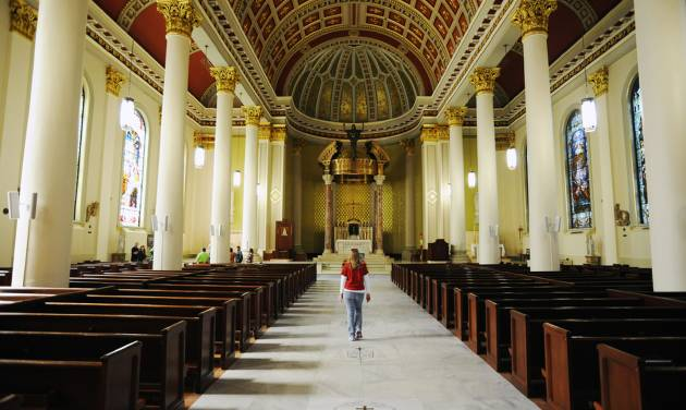 """A tourist walks in the Cathedral Basilica of the Immaculate Conception in Mobile, Ala., on Saturday, March 1, 2014. Mobile is that """"other"""" city on the northern Gulf Coast, the one that sometimes gets lost between the beaches of the Florida Panhandle and New Orleans. The church is among the free attractions in Mobile. (AP Photo/Jay Reeves)"""