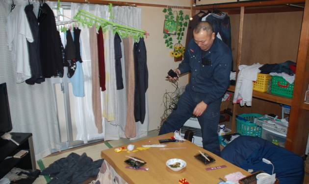 In this Friday, March 1, 2013 photo, truck driver Takahiro Ishitani picks up his mobile phone in his home in Minami-Soma, Fukushima prefecture, Japan. Japan's radiation nightmare has turned Ishitani's life upside down, and the lively home he once shared with his wife and three sons into a cluttered bachelor pad, two years after an earthquake and tsunami caused meltdowns and explosions at the Fukushima Dai-ichi nuclear power plant that sent his family and many other residents fleeing. (AP Photo/Malcolm Foster)