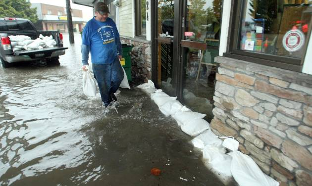 Building owner Darvin Ecklund places sandbags in front of the About Floors and West Sound Crossfit storefronts on Bay Street in Port Orchard, Wash., on Monday, Nov 19, 2012. Heavy rains inundated the areas storm drains and caused flooding in the Port Orchard downtown district and elsewhere in Kitsap County. (AP Photo/Kitsap Sun, Meegan M. Reid)