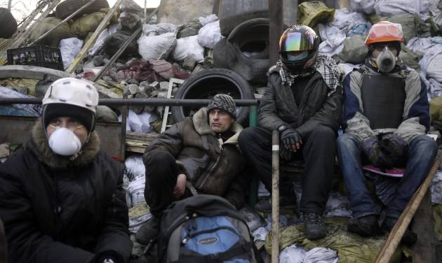 Anti-government protesters take a break on a barricade at Independence Square in Kiev, Ukraine, Friday, Feb. 21, 2014. Ukraine's presidency said Friday that it has negotiated an international deal intended to end battles between police and protesters that have killed scores and injured hundreds. (AP Photo/ Marko Drobnjakovic)