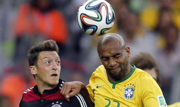 Germany's Mesut Ozil, left, and Brazil's Maicon go for a header during the World Cup semifinal soccer match between Brazil and Germany at the Mineirao Stadium in Belo Horizonte, Brazil, Tuesday, July 8, 2014. (AP Photo/Frank Augstein)